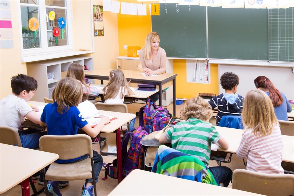 Eine Lehrerin steht vorne und unterrichtet die Klasse.