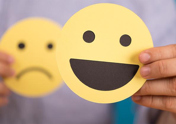 Ein lachendes Smiley wird in den Vordergrund gehalten und ein trauriges Smiley erkennt man im Hintergrund.