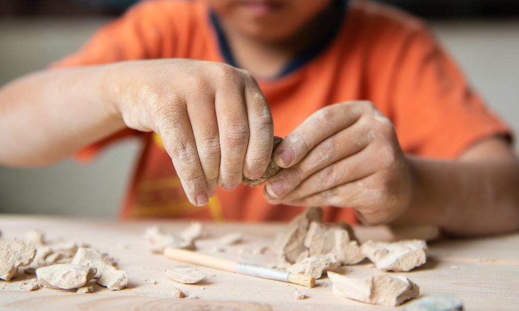 Ein Kind säubert archäologische Funde.