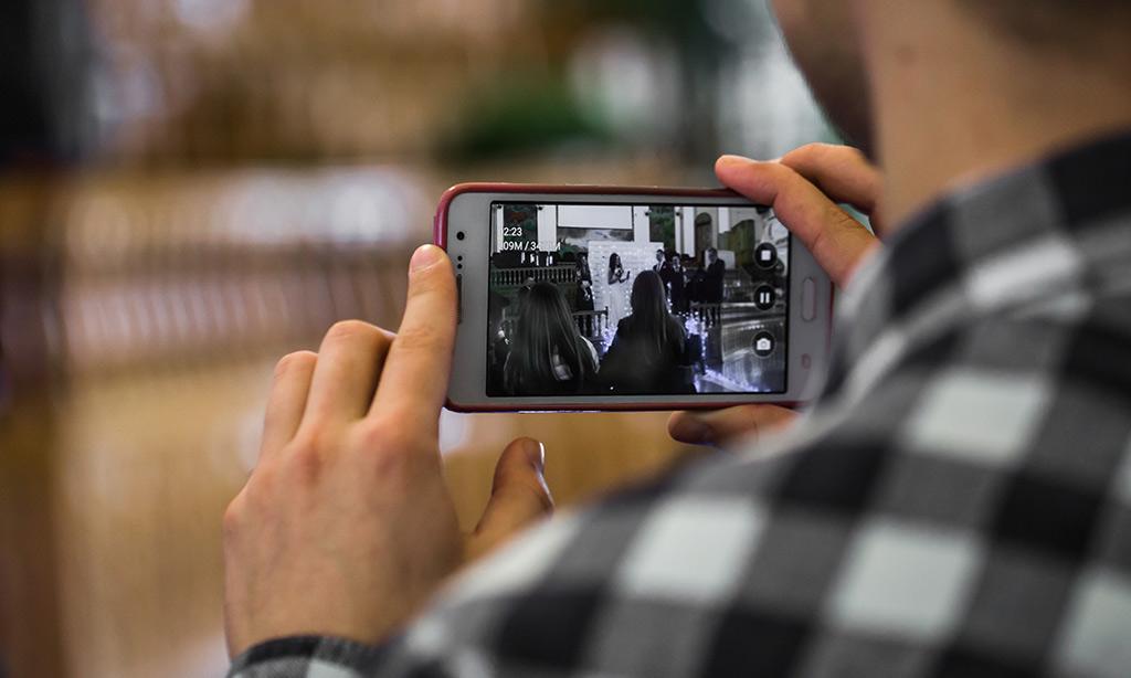 Ein Mann filmt mit seinem Handy