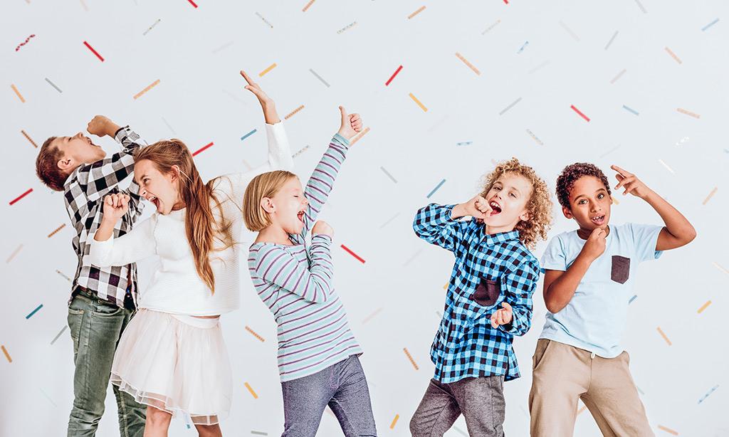 Fünf Kinder singen und Konfetti fällt auf sie herunter.