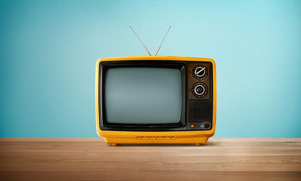 Ein oranger Fernseher steht auf einem Tisch vor einer blauen Wand.