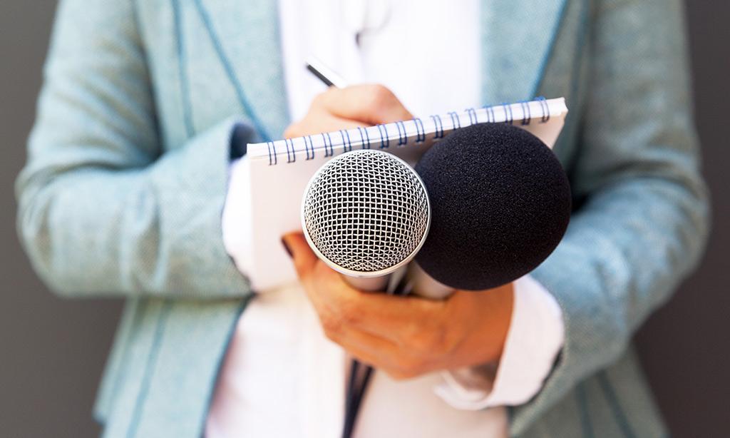 Eine Frau nimmt Notizen und hat ein Mikrofon in der Hand