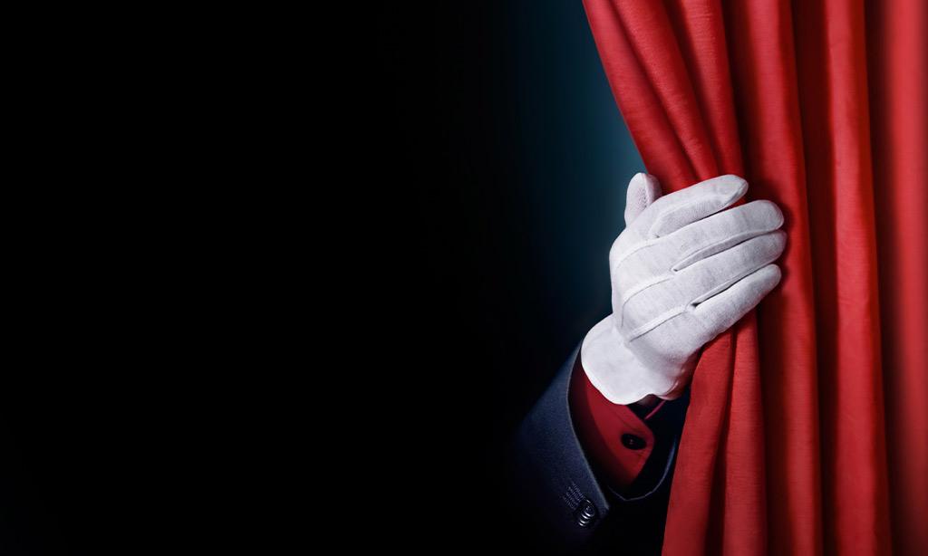 Eine Hand in einem weißem Handschuh schiebt einen roten Kinovorhang zur Seite.