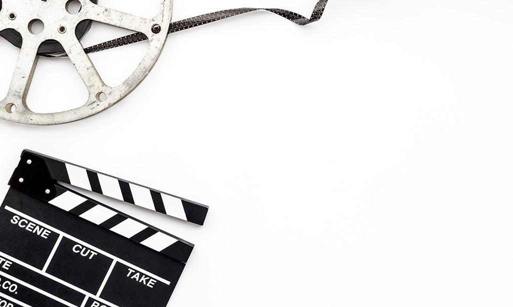 Eine Filmklappe und eine Filmrolle auf weißem Hintergrund