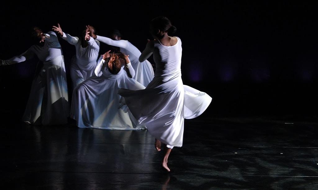 Frauen tanzen in weißen Kleidern.