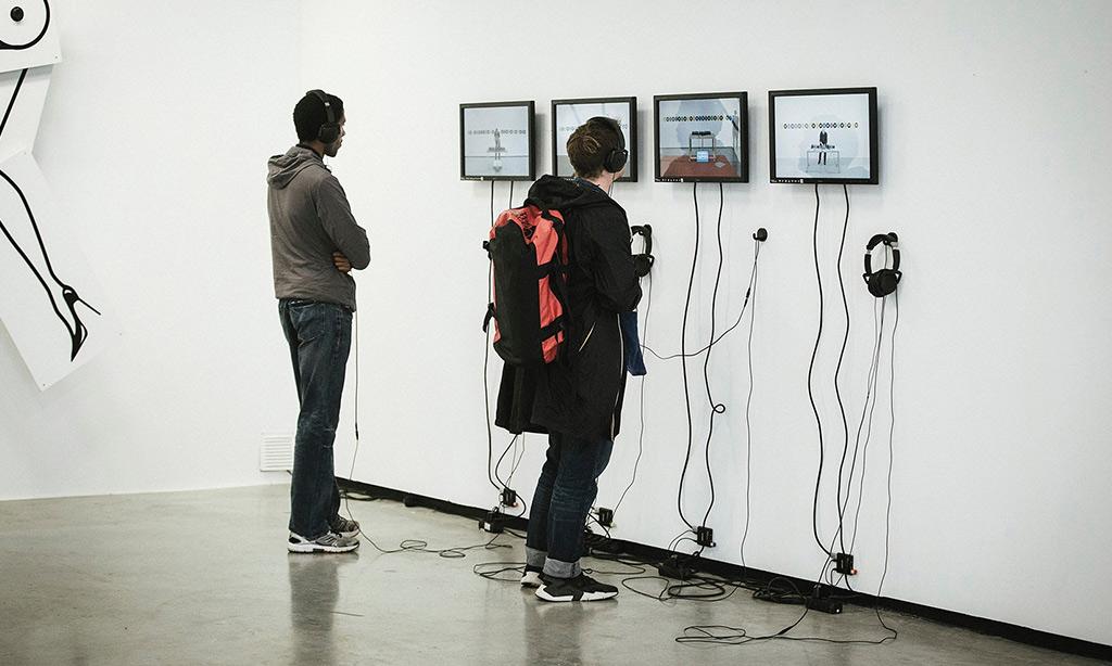 Zwei Personen schauen sich im Museum auf Bildschirmen etwas an