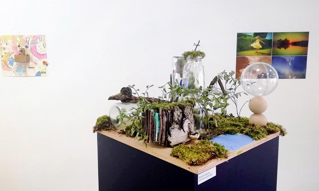 Eine aus Moos, Holz, Blättern und Glas gebastelte Naturlandschaft.