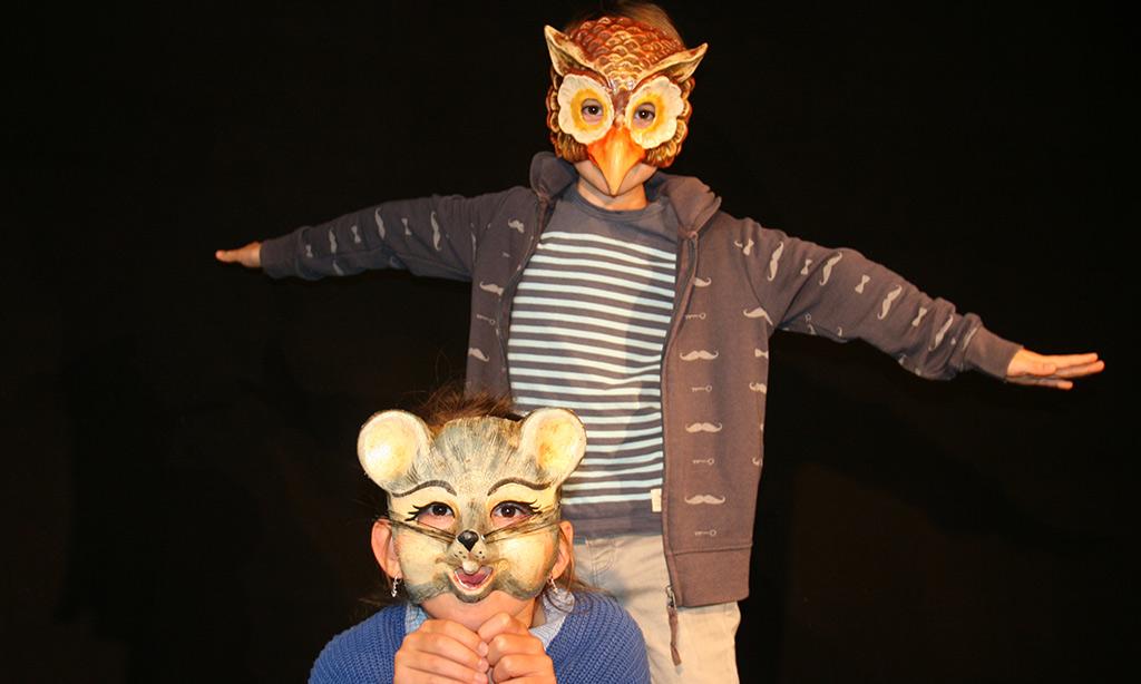 Zwei Kinder spielen mit Masken Theater.