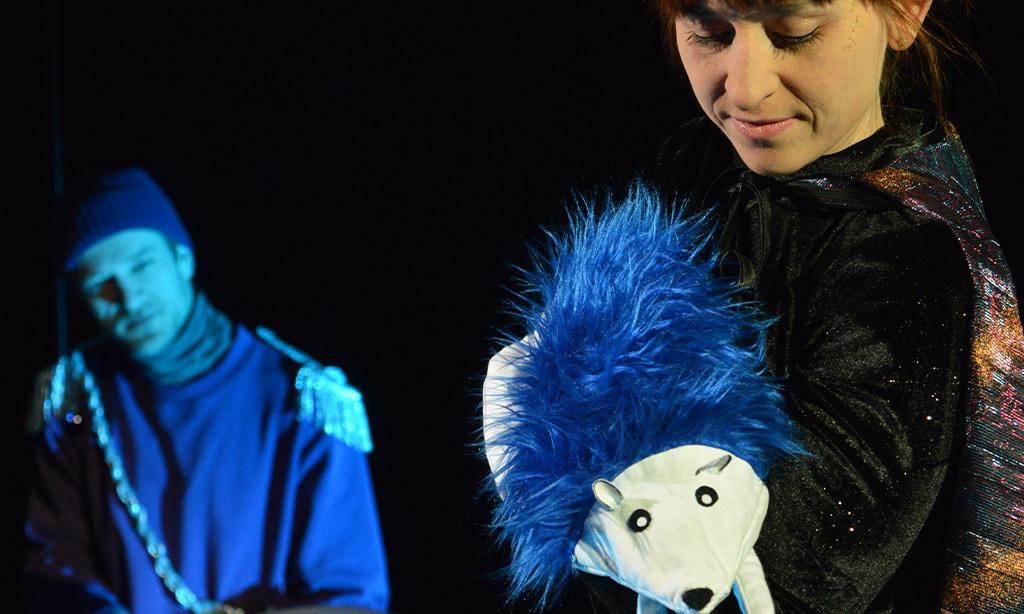 Frau spielt Thater mit einem blauen Igel und ein Mann trommelt im Hintergrund.