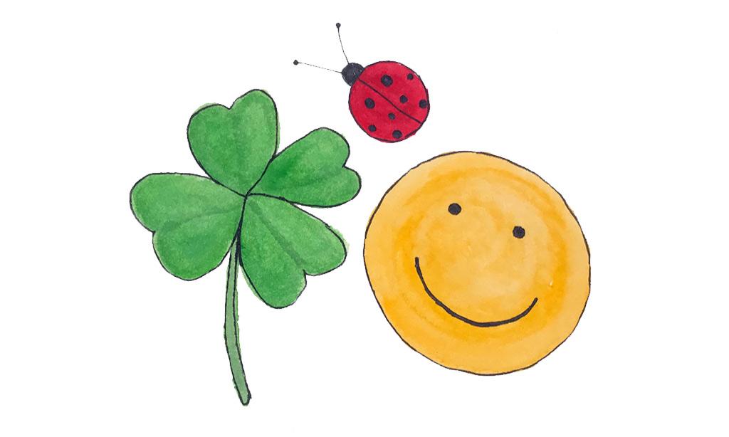 Ein gemaltes Kleeblatt, ein Marienkäfer und ein Smiley.