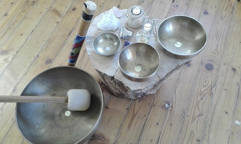 verschiedene Klangschalen, ein Regenmacher und Kerzen.
