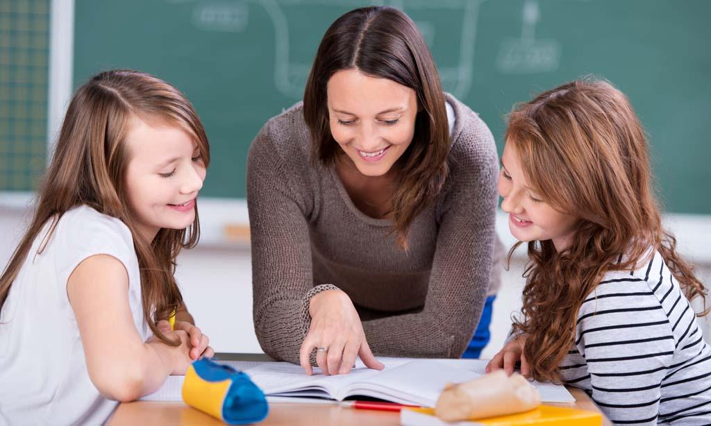 Eine Lehrerin erklärt zwei Schülerinnen etwas.